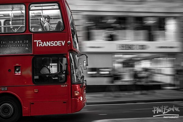 This photo shows the front of a red double decker bus travelling across a city
