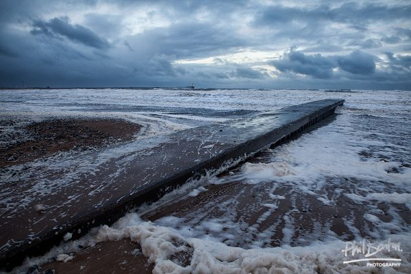 This photo shows white in colour and foamy sea water over the rocks at Blyth Northumberland